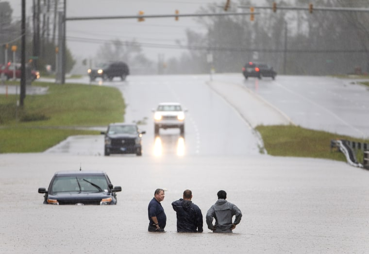 Image: Bystanders help a stranded motorist after floodwaters from Hurricane Florence