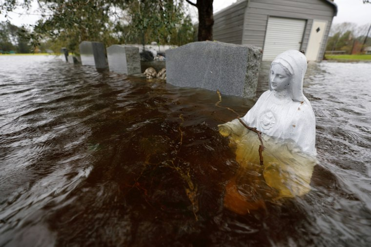 Image: A Christian statuette is partially submerged in rising flood waters inundating a cemetery in the aftermath of Hurricane Florence, in Leland, North Carolina