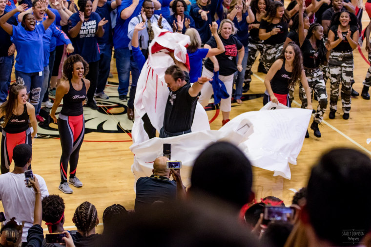 At the end of the pep rally performance, Lake Mary High School's head football coach tore apart a banner bearing insults from the school's cross-town rival.