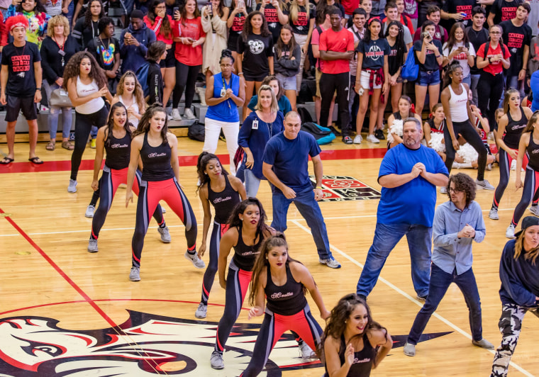 Lake Mary High School teachers and administrators (wearing blue shirts) joined the school's dance team, the Lake Marionettes, for a pep rally dance performance.