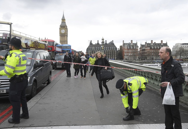 Image: A woman ducks under a police tape after an incident on Westminster Bridge in London