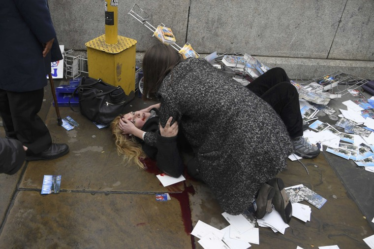 Image: A woman lies injured after a shotting incident on Westminster Bridge in London