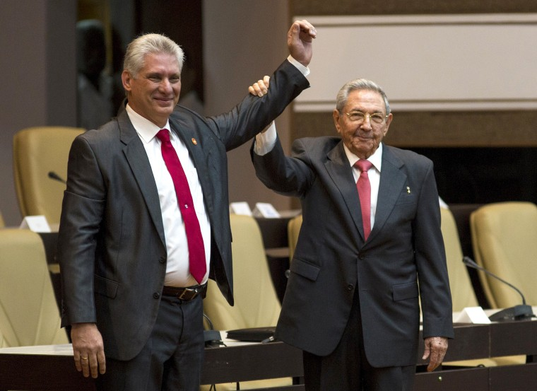 Image: Cuba's new president Miguel Diaz-Canel, left, and former president Raul Castro, raise their arms after Diaz-Canel was elected