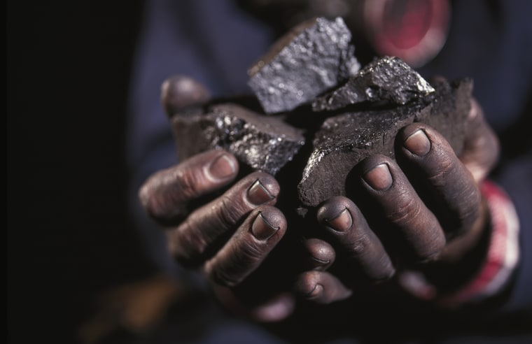 Image: Hands holding lumps of coal