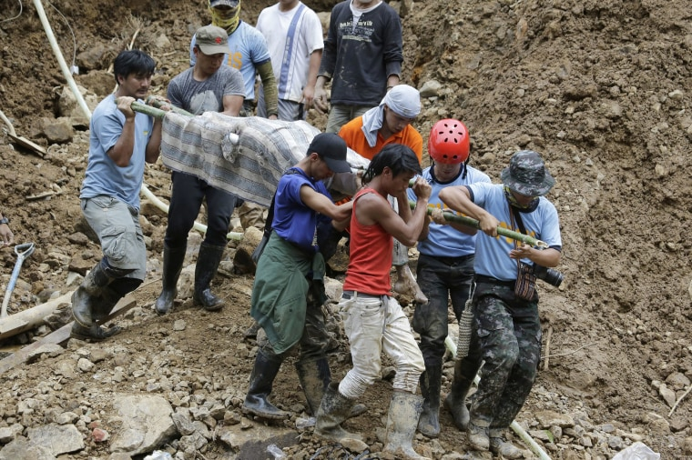 Image: Rescuers carry a body from the site where victims are believed to have been buried by a landslide