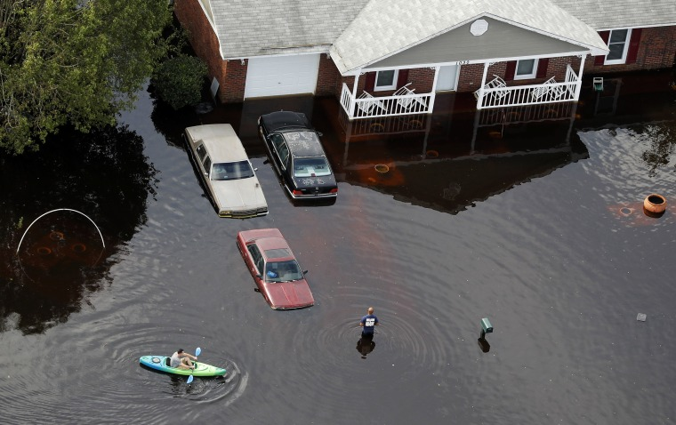 Image: A man paddles a kayak in a flooded neighborhood in the aftermath of Hurricane Florence, in Fayetteville