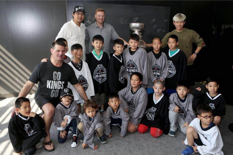 Todd Elik, head coach of the Beijing Jr. Kings, left, and goalie coach Mitch O'Keefe, wearing grey shirt, pose with members of the Beijing Jr. Kings.