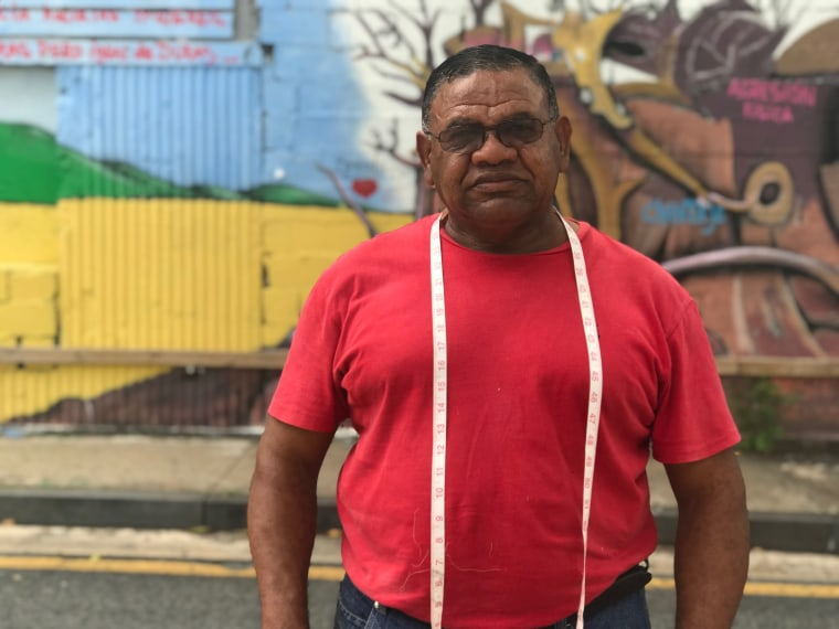 "Porfirio ""Pachin"" Guerrero, who's worked as a tailor for more than 30 years, poses in front of a mural in Rio Piedras, Puerto Rico."