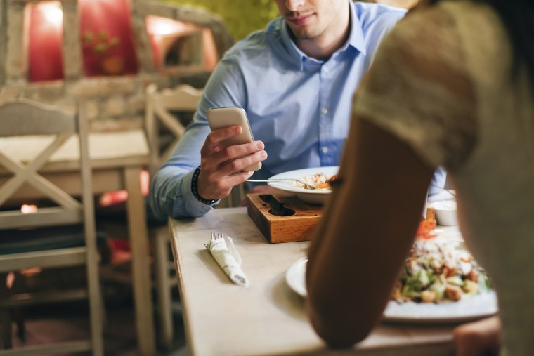 Image: Man checking messages while having dinner in a restaurant