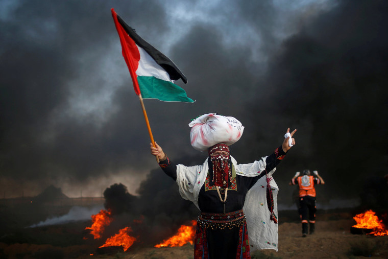 Image: Woman holds a Palestinian flag during a protest at the Israel-Gaza border fence, east of Gaza City