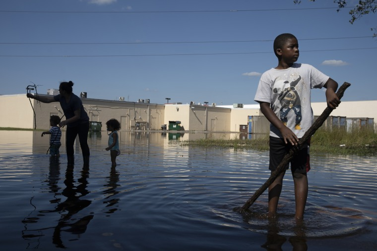 Image: Xavier Hamilton plays in floodwater in front of their home in Lumberton, North Carolina