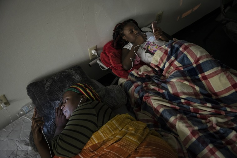 Image: Shekila Dupris and her daughter Nia rest in a church shelter after being forced out of her home due to flooding in Lumberton
