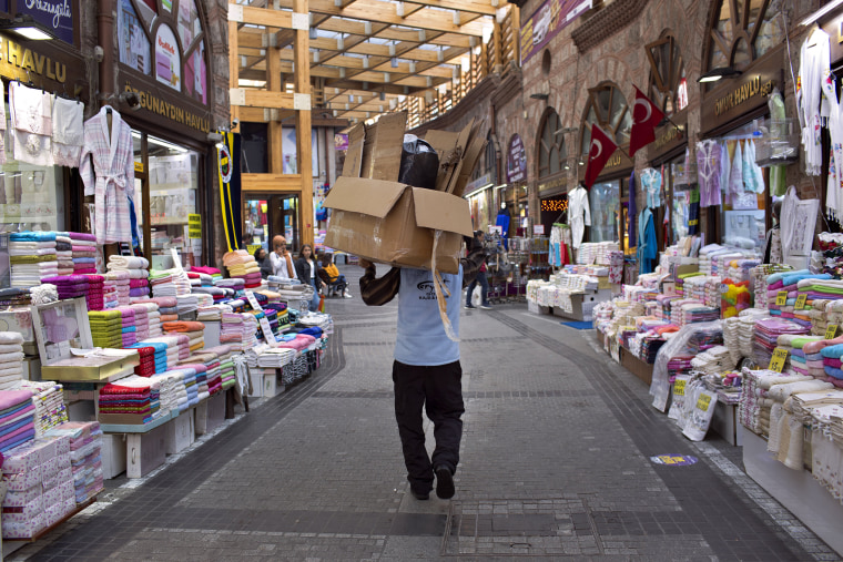 Image: A man carries empty cardboard boxes through a market in Bursa, Turkey.