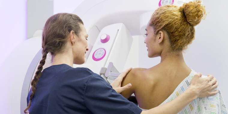 Hospital Radiographer Giving Mammogram To Female Patient