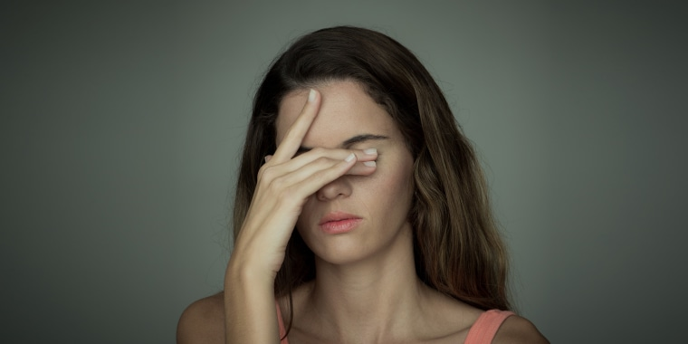 Young woman covering her eyes with one hand