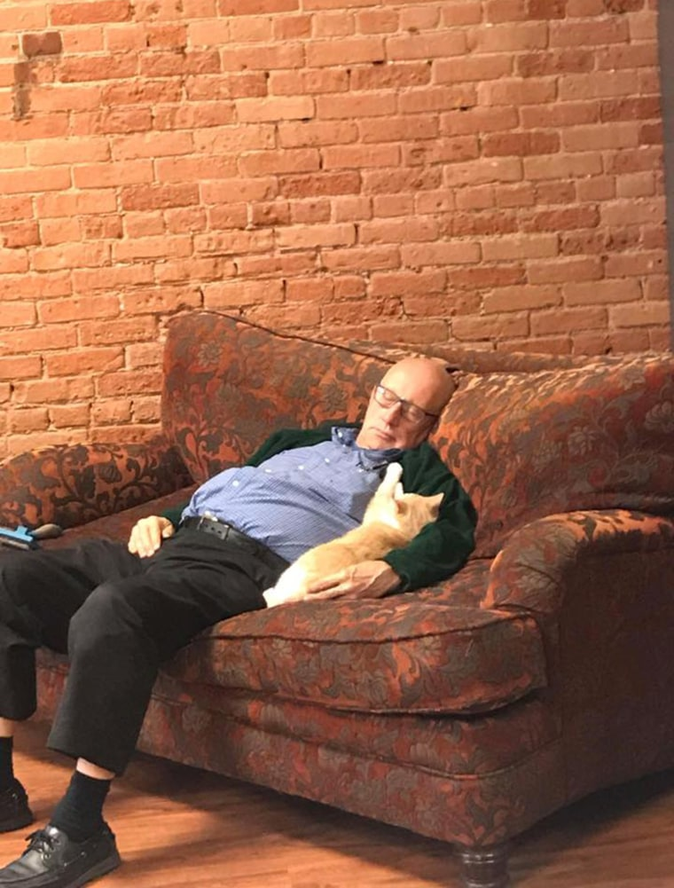 volunteer Terry sleeping with sanctuary cat