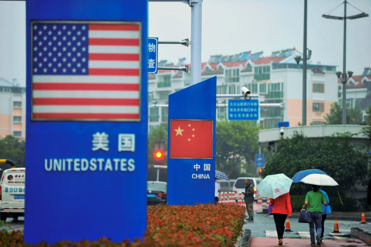 Image: Signs featuring U.S. and Chinese flags are seen outside a store selling foreign goods in Qingdao, China
