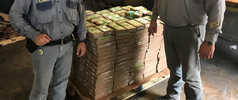 Officers with the Texas Department of Criminal Justice pose with the packets of cocaine that were discovered in the bananas.