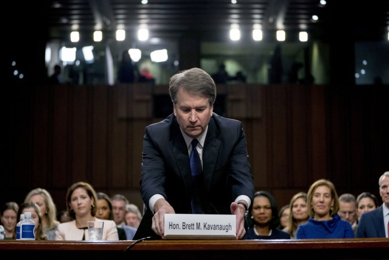 Image: Brett Kavanaugh fixes his name sign after being sworn in as he appears before the Senate Judiciary Committee