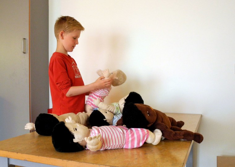 Image: A boy plays with dolls at the Hjalli elementary school