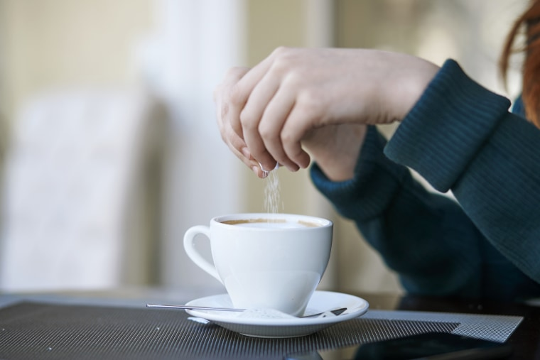 Woman pouring sugar into coffee