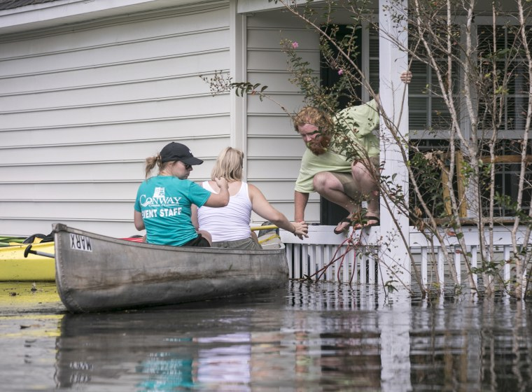 Image: David Covington jumps from a porch railing to his canoe in Conway, South Carolina
