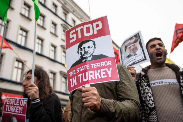 Image: A demonstrator holds a banner depicting Turkish President Erdogan in Berlin