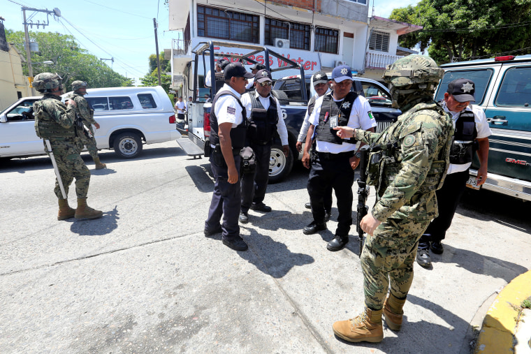 Mexican Marines escort municipal police officers disarmed and detained during an operation to check if they colluded with organised crime, in Acapulco