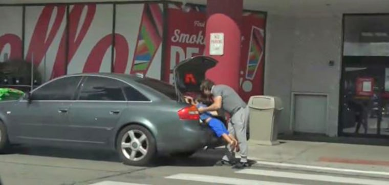 Boguslaw Matlak places his son in the trunk of his car during what he said was a hidden camera experiment.