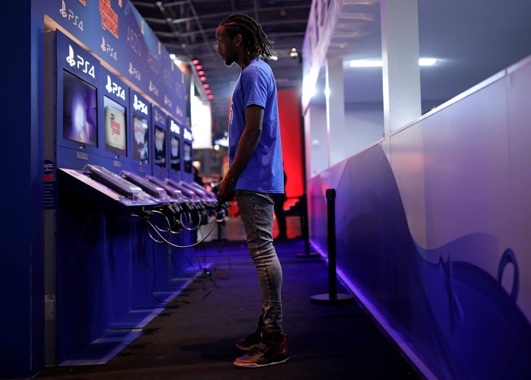 An  attendee plays a video game on a PlayStation 4 (PS4) at the Paris Games Week