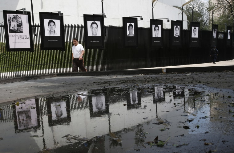 Photographs of the teachers college students who disappeared on Sept. 26, 2014 hang on the fence surrounding the senate building in Mexico City on  Sept. 26, 2018.