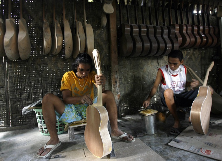 Image: Workers assemble guitars at a private gu