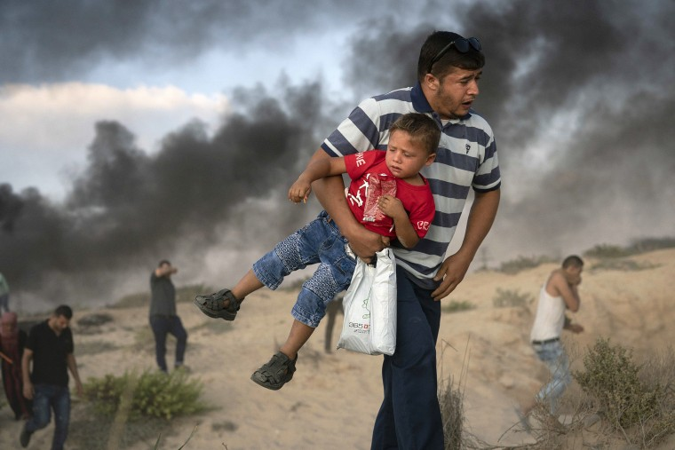 Image: A Palestinian protester carries a boy as he runs from tear gas in Beit Lahiya, northern Gaza Strip.