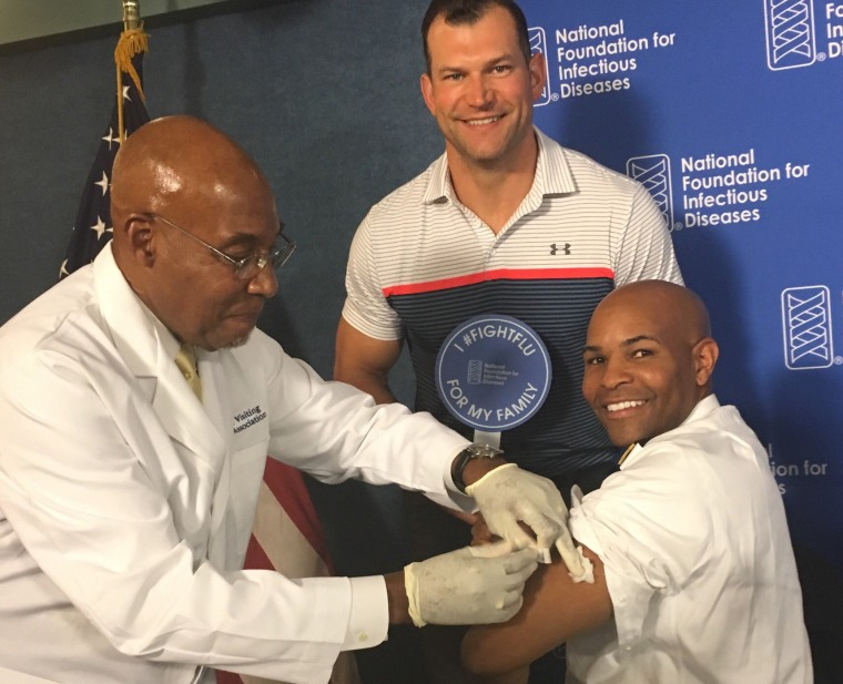 Surgeon General Jerome Adams receives a flu shot as former Cleveland Browns offensive tackle Joe Thomas looks on.