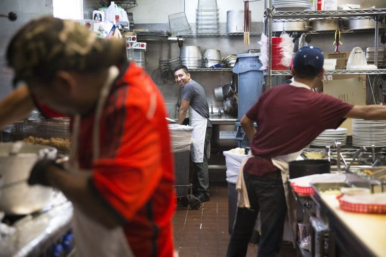 Image: Uber Dorantes, Miguel Angel, and Cristian Lopez work in the kitchen at Taqueria del Sol