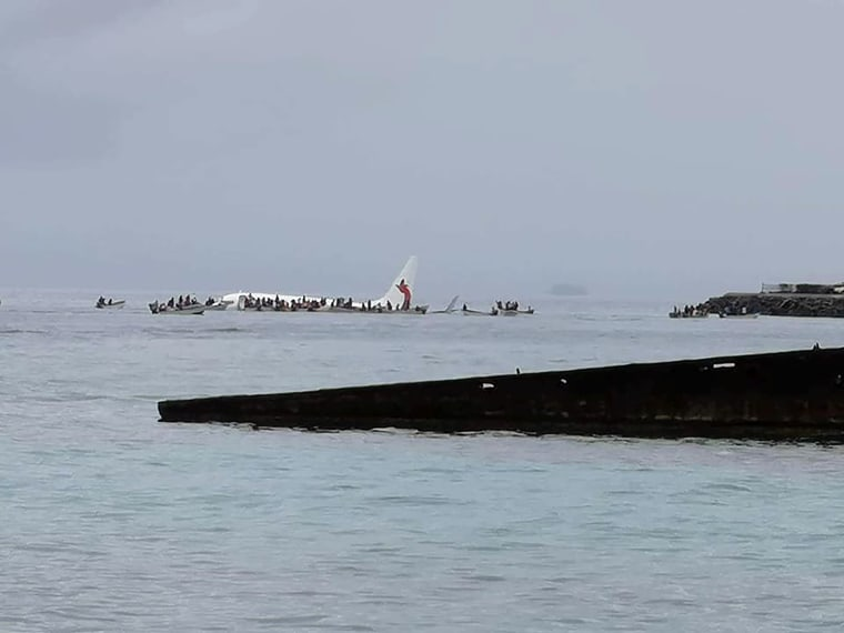 Image: People are evacuated from an Air Niugini plane which crashed in the waters in Weno, Chuuk, Micronesia