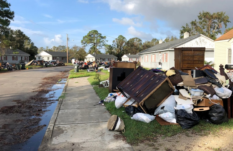 Residents in New Bern, North Carolina, drag their belongings damaged by Hurricane Florence to the side of the road on Sept. 27, 2018.