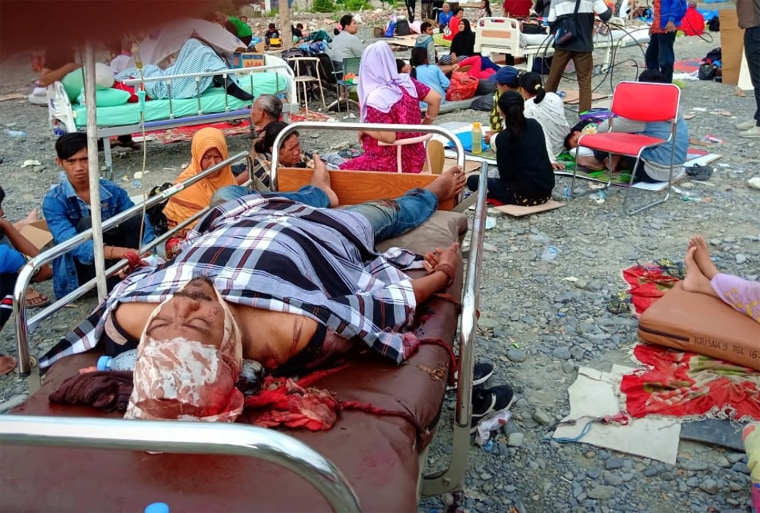 Image: Survivors rest on trollies outside a hospital in Palu, Indonesia.