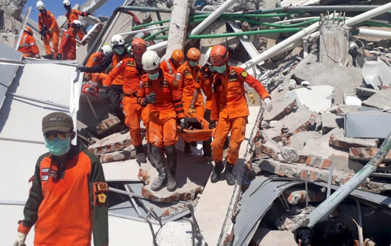 Image: A search and rescue team evacuates a victim from the ruins of the Roa-Roa Hotel in Palu, Central Sulawesi,