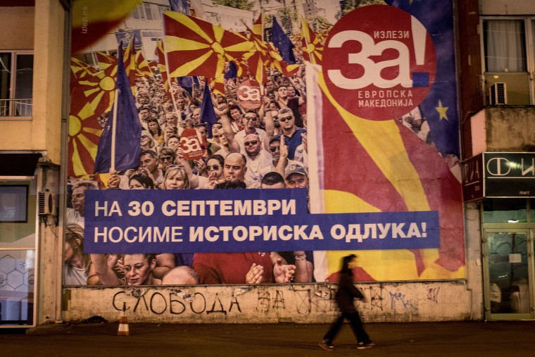 Image: People walk past a referendum poster saying 'Yes for European Macedonia'