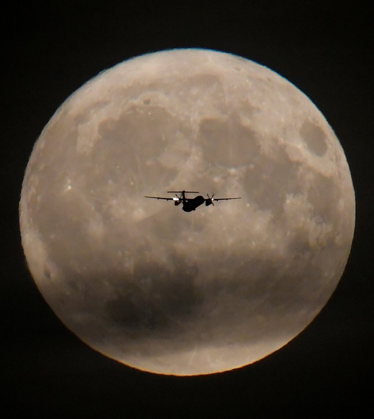Image: A passenger plane is seen with the full moon behind as it begins its final landing approach to Heathrow Airport in London, Britain