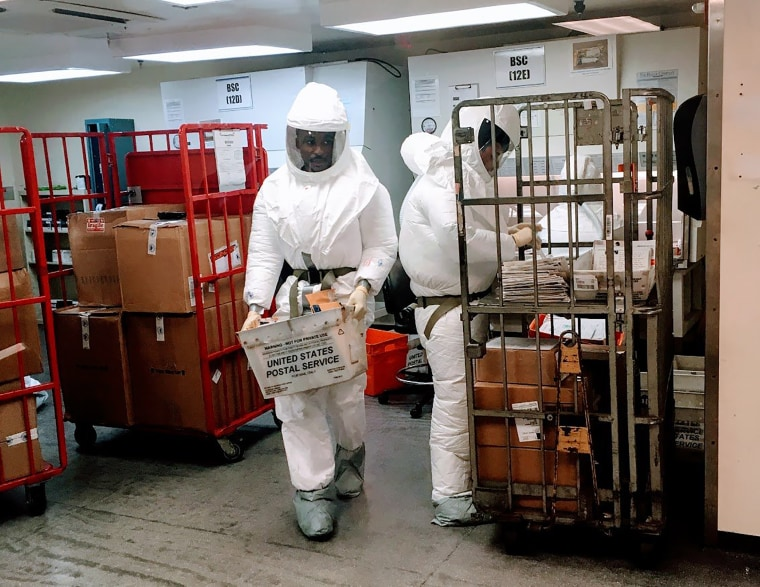 U.S. Defense Department personnel, wearing protective suits, screen mail as it arrives at the Pentagon