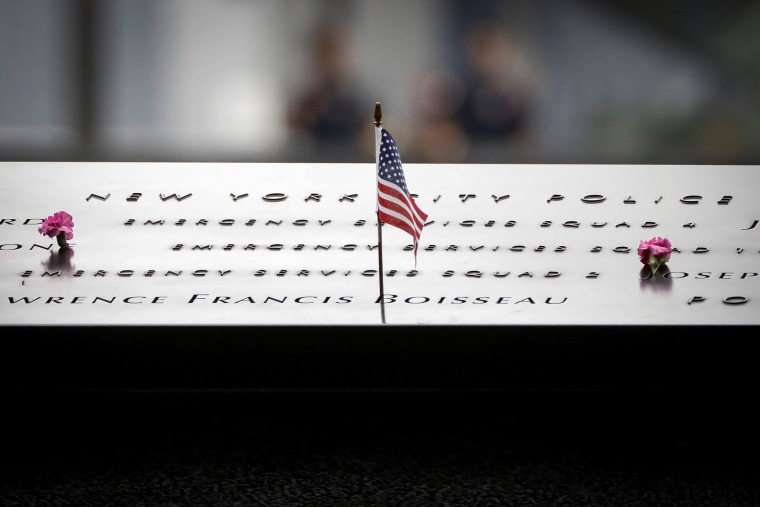 Image: Flowers and a flag are left on names on the National 9/11 Memorial during ceremonies marking the 17th anniversary of the September 11, 2001 attacks on the World Trade Center, at the National 9/11 Memorial and Museum in New York