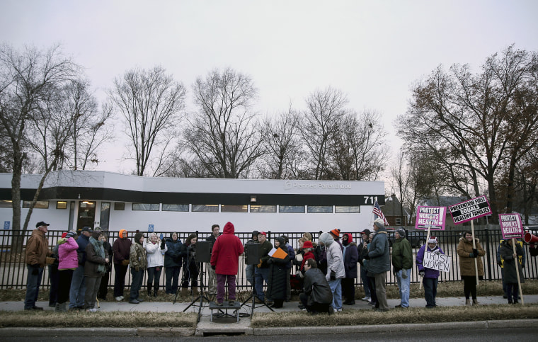 Anti-abortion advocate Joanne Schrader of Fulton (in red) speaks during a news conference organized outside the Planned Parenthood Columbia Health Center on Dec. 12, 2016 in Columbia, Missouri.
