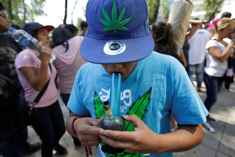A Teenager smokes marijuana out of a bong during a 4/20 party to demand legalization and to celebrate marijuana culture outside the Senate building in Mexico City
