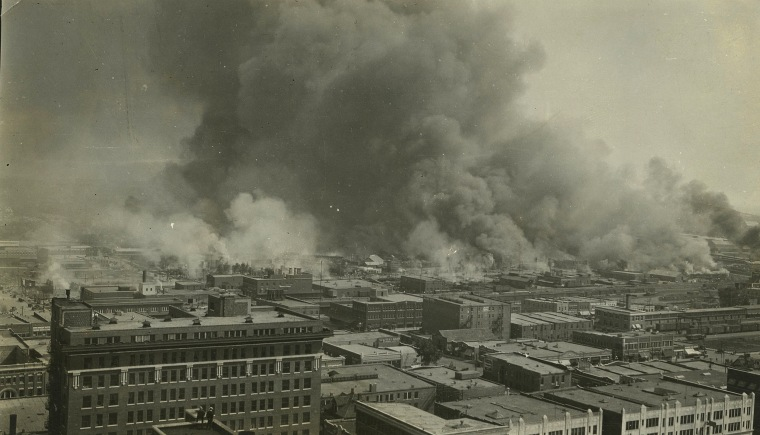 Image: Smoke rises over Tulsa's Greenwood District during race riots in 1921