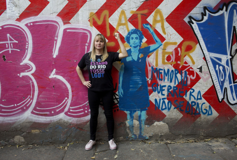 Image: Barbara Aires, 35, poses for a photo next to a mural of slain councilwoman Marielle Franco in Rio de Janeiro, Brazil