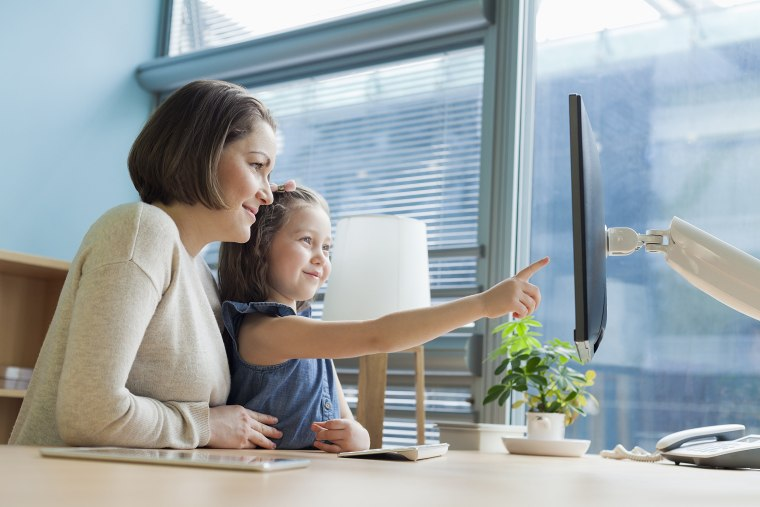 Image: Mother and daughter looking at work desk computer