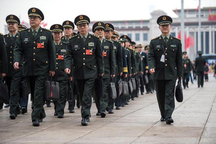 Military delegates arrive for the fifth plenary session of the first session of the 13th National People's Congress (NPC) in Beijing on March 17, 2018.