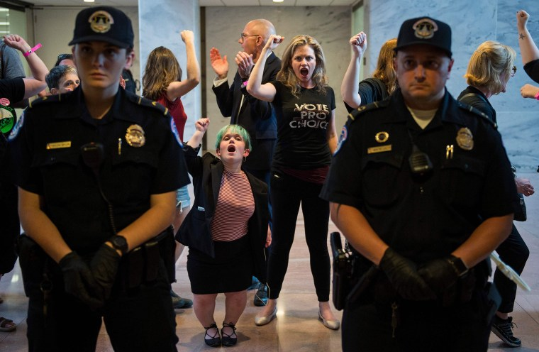 Police look on as protesters are arrested in the Hart Senate Office Building during a rally against Supreme Court nominee Brett Kavanaugh on Capitol Hill on Oct. 4, 2018.